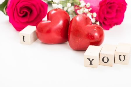 Two red hearts and roses, and wooden cubes with words I and You, on white background. I love you concept.