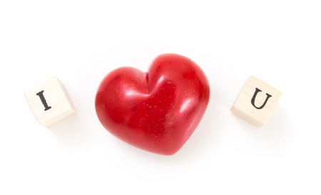 Red heart and wooden cubes with I and U, on white background. I love you concept. Stock Photo