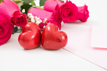 Two red hearts with pink envelope and red roses closeup. Stock Photo