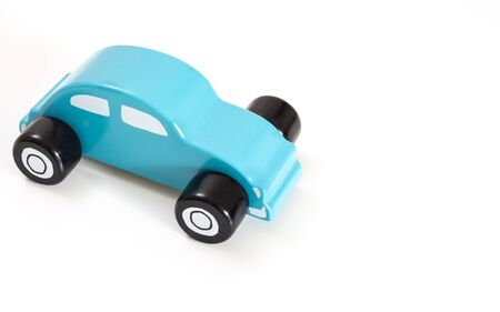 A blue toy car, on white background with copy-space.