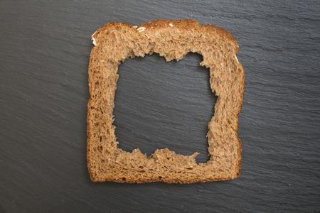 Whole grain sandwich bread slice with hole, on dark surface/ background. Reklamní fotografie