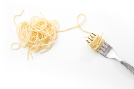 Duidelijk gekookte spaghettideegwaren op vork, op witte achtergrond.