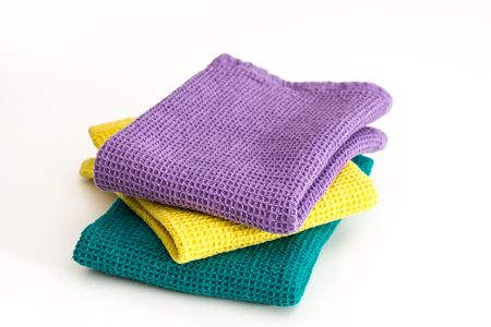 Stack of  folded colorful kitchen towels, on white background. Stock Photo