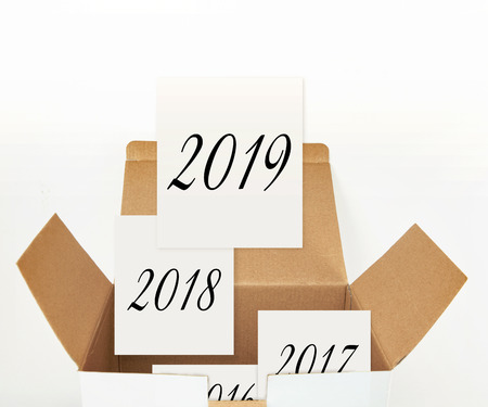Cards with 2019, 2018 etc. years in opened cardboard box , on white background