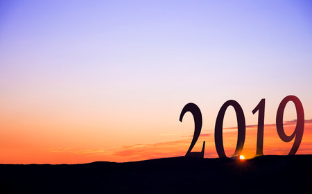2019 in huge numbers, on dark mountains silhouettes, with vivid and beautiful sunrise as background.