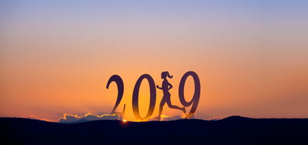 2019 On dark mountains with silhouette of a woman running and sunrise as background. Stockfoto
