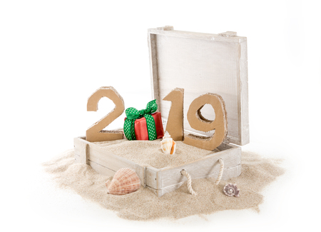 2019, handmade 3D numbers made of reused cardboard paper, in wooden chest with sand and on white background. Stock Photo