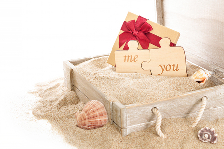Opened wooden chest with gift box and two puzzle pieces, on sand and white background.