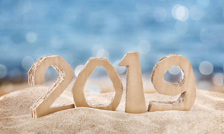 2019 handmade numbers made of reused cardboard paper with gift box , on sand and sea background. Stock Photo