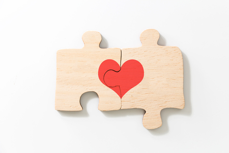 Two joined pieces of wooden puzzle, with red heart, on white background. Фото со стока