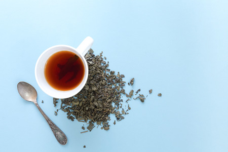 Cup of freshly brewed green tea with heap of dried leaves, on blue background.