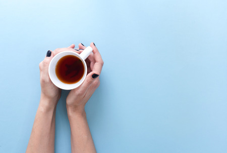 Hands holding a cup of freshly brewed green tea, flat lay on blue background.
