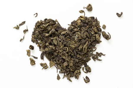 Heart made of green dry tea, on white background.