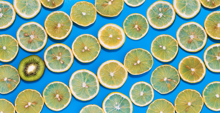 Lemon slices and one piece kiwifruit, arranged in lines with hard shadows on blue background, flat lay image. Zdjęcie Seryjne