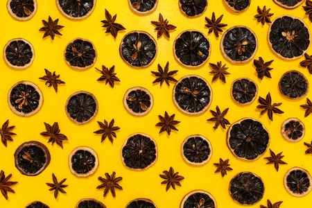 Star anise and dried lemon slices in lines with hard shadow on yellow background, flat lay image.
