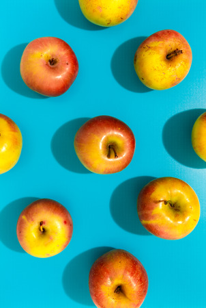 Apples with hard shadow on blue background, flat lay image.