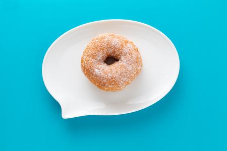 Una ciambella ricoperta di zucchero su un piatto a forma di bolla di testo, su sfondo blu.