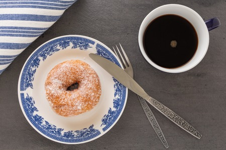 A cup of coffee, a plate with sugar coated doughnut and other breakfast objects on tabletop. Stockfoto