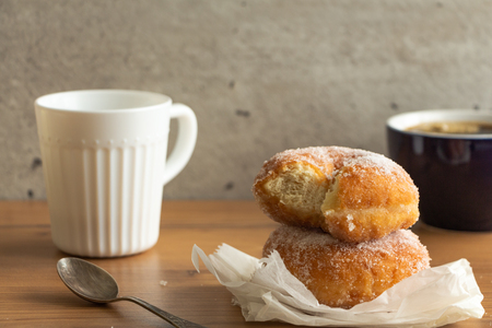 Sugar coated doughnuts on crumpled paper with a two cups of coffee , on wooden tabletop.