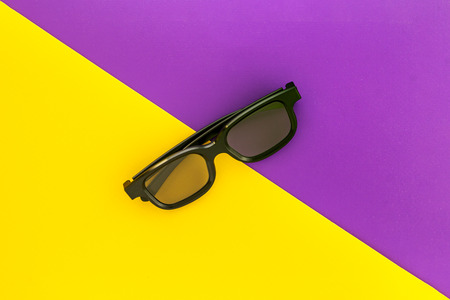 Black 3D glasses, on fun vivid purple yellow background. Flat lay.