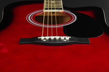 Closeup of a six stringed red acoustic guitar, from bridge side. Music entertainment background.