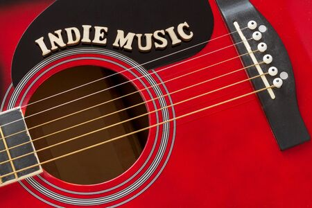 Words Indie Music with wooden letters, closeup on a surface of red acoustic guitar. Music entertainment background.