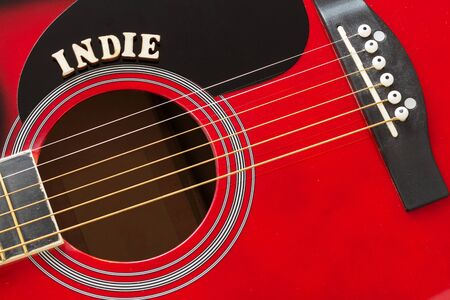 Word Indie with wooden letters, closeup on a surface of red acoustic guitar. Music entertainment background.