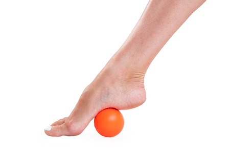rubber ball: Massage feet with a rubber ball in orange on an isolated white background. Stock Photo