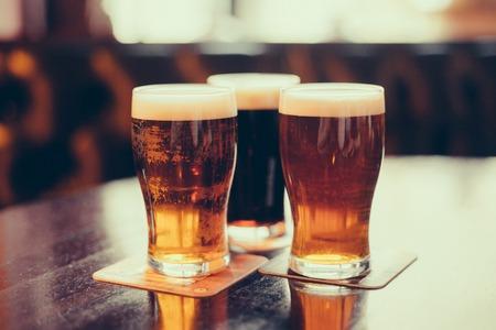 vasos de cerveza: Vasos de cerveza clara y oscura sobre un fondo pub. Foto de archivo