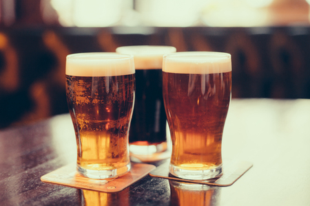 Gläser helles und dunkles Bier auf einem Pub Hintergrund. Standard-Bild