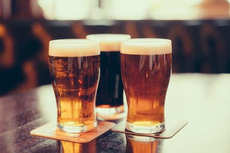 Verres de bière légère et sombre sur un fond de pub. Banque d'images