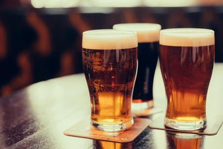 barra de bar: Vasos de cerveza clara y oscura sobre un fondo pub. Foto de archivo