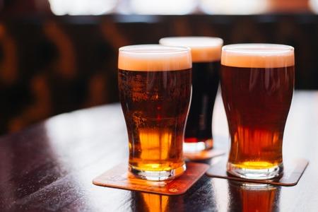 Vasos de cerveza clara y oscura sobre un fondo pub.