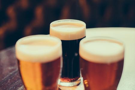 Vasos de cerveza clara y oscura sobre un fondo pub. Foto de archivo