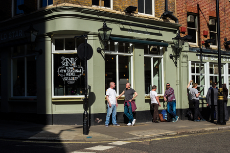 socialising: LONDON, UK - APRIL15, 2015: Exterior of pub in London with lots of people drinking and socialising after work. Editorial