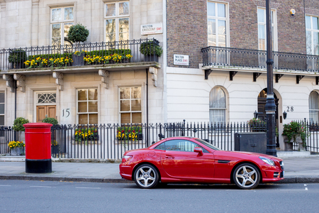 typically british: LONDON, UK - April, 14: Houses in London, english architecture. Red Mercedes parked near the house and red mailbox.