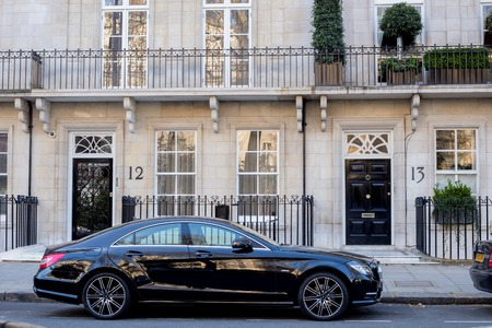 LONDON, UK - April, 14: Houses in London, english architecture. Luxury black Mercedes, Executive car parked near the house. Editorial