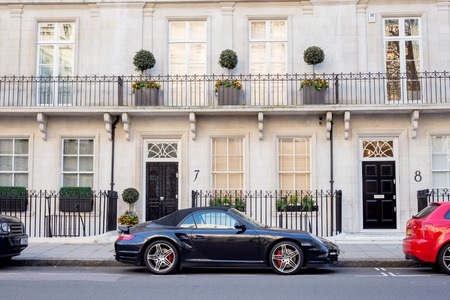 typically british: LONDON, UK - April, 14: Luxury black Porsche. Houses in London, english architecture