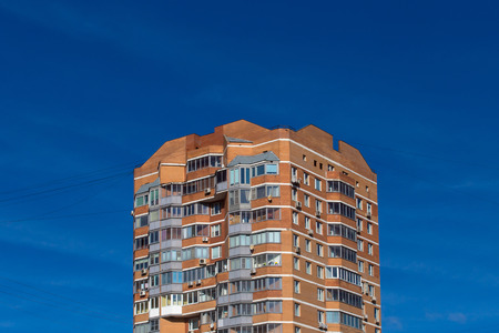 storey: Apartment building against blue sky. Top- a place for your text.