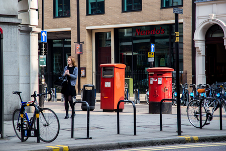 shaftesbury: LONDON, UK - April 08, 2015: girl standing alone on the streets of London, there are a lot of bicycles
