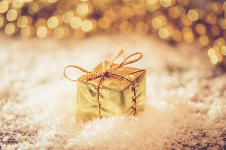 Christmas retro gold box in the snow with Christmas background light on wooden table. golden and white ornaments Stock Photo