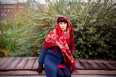 Girl sits in a russian red scarf on a bench Stock Photo