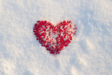 Red heart lies on the snow, the symbol of Valentines Day, heart melts snow