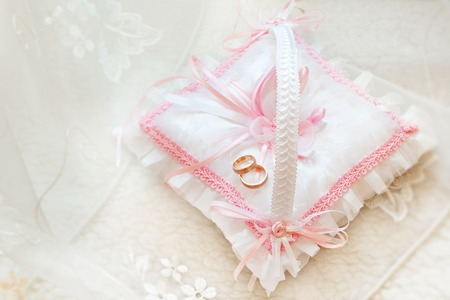 customary: gold wedding rings on a pillow