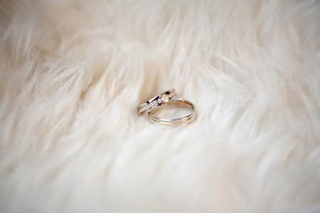 customary: gold wedding rings on a white fur Stock Photo