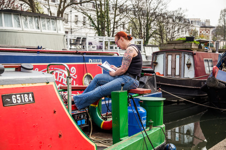 regent: UK, London - April 08, 2015: Woman reading a book sitting on a barge. Regents canal, Little Venice in London