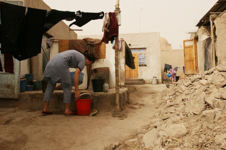 disadvantaged: Khiva, Uzbekistan - March 08, 2009: Woman hanging laundry after washing Editorial