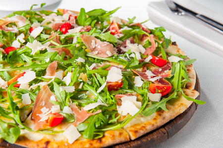 Selective focus Close up Delicious Pizza with hamon and cherry tomato slices, parmezan cheese and arugula on the wooden board on the served restaurant table Stock Photo