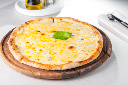 Four cheese pizza quattro fromaggi with basil leaf on a rustic wooden board on the served restaurant table