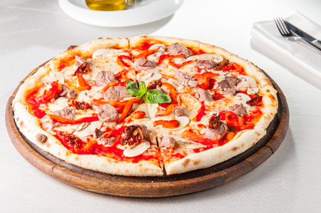 Tasty, flavorful Pizza with veal and mushrooms on the wooden board on the served restaurant table Stock Photo